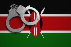 De vlag en de politiehandcuffs van Kenia Het concept misdaad en inbreuken in het land stock fotografie