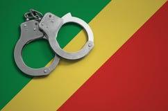 De vlag en de politiehandcuffs van de Kongo Het concept misdaad en inbreuken in het land stock afbeeldingen