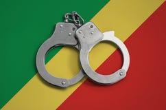 De vlag en de politiehandcuffs van de Kongo Het concept naleving van de wet in het land en bescherming tegen misdaad royalty-vrije stock afbeeldingen