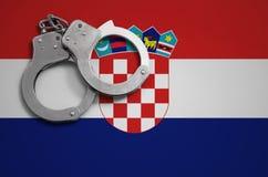 De vlag en de politiehandcuffs van Kroatië Het concept misdaad en inbreuken in het land stock foto's