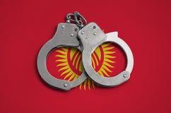 De vlag en de politiehandcuffs van Kyrgyzstan Het concept naleving van de wet in het land en bescherming tegen misdaad stock afbeelding