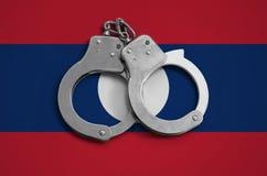 De vlag en de politiehandcuffs van Laos Het concept naleving van de wet in het land en bescherming tegen misdaad stock fotografie
