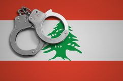 De vlag en de politiehandcuffs van Libanon Het concept misdaad en inbreuken in het land royalty-vrije stock afbeeldingen