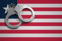 De vlag en de politiehandcuffs van Liberia Het concept misdaad en inbreuken in het land royalty-vrije stock afbeeldingen