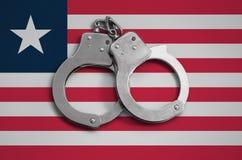 De vlag en de politiehandcuffs van Liberia Het concept naleving van de wet in het land en bescherming tegen misdaad royalty-vrije stock fotografie