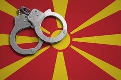 De vlag en de politiehandcuffs van Macedonië Het concept misdaad en inbreuken in het land stock fotografie