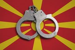 De vlag en de politiehandcuffs van Macedonië Het concept naleving van de wet in het land en bescherming tegen misdaad royalty-vrije stock foto's