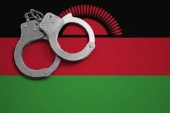 De vlag en de politiehandcuffs van Malawi Het concept misdaad en inbreuken in het land stock foto