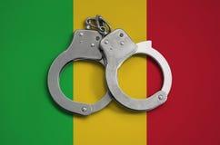 De vlag en de politiehandcuffs van Mali Het concept naleving van de wet in het land en bescherming tegen misdaad royalty-vrije stock afbeeldingen