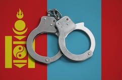 De vlag en de politiehandcuffs van Mongolië Het concept naleving van de wet in het land en bescherming tegen misdaad royalty-vrije stock foto