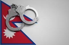 De vlag en de politiehandcuffs van Nepal Het concept misdaad en inbreuken in het land royalty-vrije stock fotografie