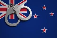 De vlag en de politiehandcuffs van Nieuw Zeeland Het concept misdaad en inbreuken in het land stock foto