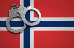 De vlag en de politiehandcuffs van Noorwegen Het concept misdaad en inbreuken in het land stock afbeeldingen
