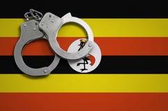 De vlag en de politiehandcuffs van Oeganda Het concept misdaad en inbreuken in het land royalty-vrije stock afbeelding