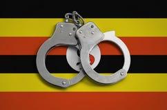 De vlag en de politiehandcuffs van Oeganda Het concept naleving van de wet in het land en bescherming tegen misdaad stock foto