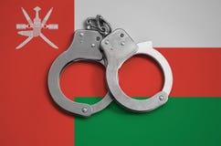 De vlag en de politiehandcuffs van Oman Het concept naleving van de wet in het land en bescherming tegen misdaad stock fotografie
