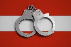 De vlag en de politiehandcuffs van Oostenrijk Het concept naleving van de wet in het land en bescherming tegen misdaad stock fotografie