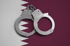 De vlag en de politiehandcuffs van Qatar Het concept naleving van de wet in het land en bescherming tegen misdaad stock fotografie