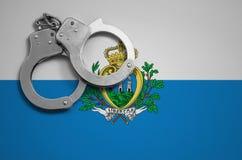 De vlag en de politiehandcuffs van San Marino Het concept misdaad en inbreuken in het land royalty-vrije stock foto