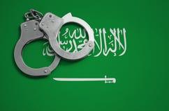 De vlag en de politiehandcuffs van Saudi-Arabië Het concept misdaad en inbreuken in het land royalty-vrije stock afbeelding