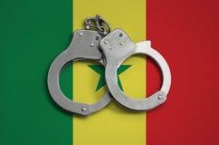 De vlag en de politiehandcuffs van Senegal Het concept naleving van de wet in het land en bescherming tegen misdaad stock foto