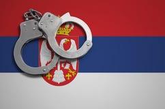 De vlag en de politiehandcuffs van Servië Het concept misdaad en inbreuken in het land royalty-vrije stock afbeelding
