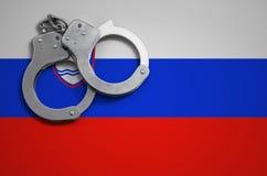 De vlag en de politiehandcuffs van Slovenië Het concept misdaad en inbreuken in het land stock foto's