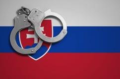 De vlag en de politiehandcuffs van Slowakije Het concept misdaad en inbreuken in het land stock foto's