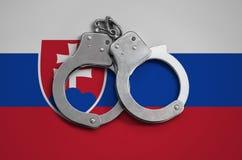 De vlag en de politiehandcuffs van Slowakije Het concept naleving van de wet in het land en bescherming tegen misdaad royalty-vrije stock fotografie