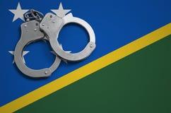 De vlag en de politiehandcuffs van Solomon Islands Het concept misdaad en inbreuken in het land stock foto's