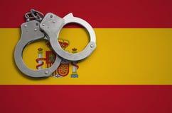 De vlag en de politiehandcuffs van Spanje Het concept misdaad en inbreuken in het land stock foto's