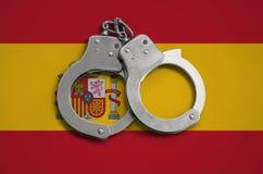 De vlag en de politiehandcuffs van Spanje Het concept naleving van de wet in het land en bescherming tegen misdaad stock foto