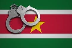 De vlag en de politiehandcuffs van Suriname Het concept misdaad en inbreuken in het land royalty-vrije stock afbeelding
