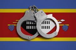 De vlag en de politiehandcuffs van Swasiland Het concept naleving van de wet in het land en bescherming tegen misdaad stock foto's