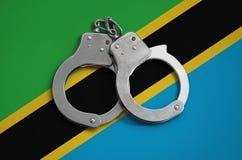De vlag en de politiehandcuffs van Tanzania Het concept naleving van de wet in het land en bescherming tegen misdaad stock foto's