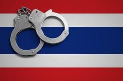 De vlag en de politiehandcuffs van Thailand Het concept misdaad en inbreuken in het land royalty-vrije stock foto