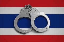 De vlag en de politiehandcuffs van Thailand Het concept naleving van de wet in het land en bescherming tegen misdaad stock afbeelding