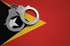 De vlag en de politiehandcuffs van Timor Leste Het concept misdaad en inbreuken in het land stock fotografie