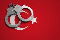 De vlag en de politiehandcuffs van Turkije Het concept misdaad en inbreuken in het land stock afbeeldingen