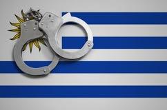 De vlag en de politiehandcuffs van Uruguay Het concept misdaad en inbreuken in het land stock foto