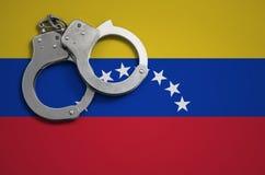 De vlag en de politiehandcuffs van Venezuela Het concept misdaad en inbreuken in het land stock foto