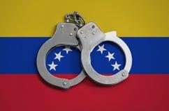 De vlag en de politiehandcuffs van Venezuela Het concept naleving van de wet in het land en bescherming tegen misdaad stock afbeelding