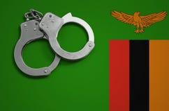De vlag en de politiehandcuffs van Zambia Het concept misdaad en inbreuken in het land stock fotografie