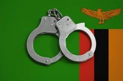 De vlag en de politiehandcuffs van Zambia Het concept naleving van de wet in het land en bescherming tegen misdaad royalty-vrije stock fotografie
