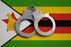 De vlag en de politiehandcuffs van Zimbabwe Het concept naleving van de wet in het land en bescherming tegen misdaad stock fotografie
