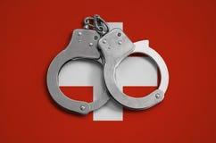 De vlag en de politiehandcuffs van Zwitserland Het concept naleving van de wet in het land en bescherming tegen misdaad royalty-vrije stock afbeelding