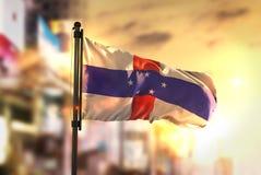 De Vlag van Antillen van Nederland tegen Stad Vage Achtergrond bij Zon Royalty-vrije Stock Foto