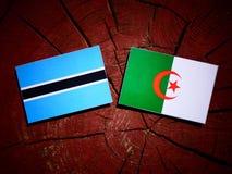 De vlag van Botswana met Algerijnse vlag op een geïsoleerde boomstomp vector illustratie