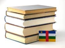 De vlag van de Centraalafrikaanse Republiek met stapel van boeken op whi worden geïsoleerd die Stock Foto's