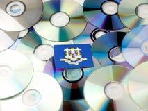 De vlag van Connecticut bovenop CD en DVD-stapel op wit wordt geïsoleerd dat Stock Fotografie